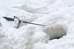 Μια ράβδος αλιείας για το χειμώνα που αλιεύει κοντά στην πάγος-τρύπα Στοκ Φωτογραφίες