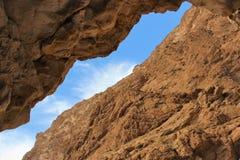 Μια ρωγμή στον απότομο βράχο που αποκαλύπτει το μπλε ουρανό στοκ εικόνα