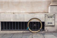 Μια ρόδα ενός ποδηλάτου που αλυσοδένεται από δύο κλειδαριές στην πρόσοψη στοκ φωτογραφίες με δικαίωμα ελεύθερης χρήσης