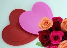 Μια ρόδινη και μια κόκκινη καρδιά με τα τριαντάφυλλα στο χαμηλότερο δικαίωμα στοκ εικόνα με δικαίωμα ελεύθερης χρήσης