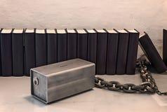 Μια σειρά των βιβλίων κοντά στον άσπρο τοίχο και ένα κιβώτιο χρημάτων μετάλλων Στοκ Φωτογραφία