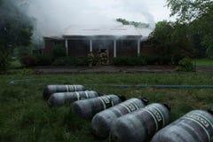 Μια σειρά των δεξαμενών μπροστά από το καίγοντας σπίτι στοκ εικόνα με δικαίωμα ελεύθερης χρήσης