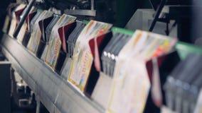 Μια σειρά των ζωηρόχρωμων τυπωμένων καρτών που κινούνται κατά μήκος της ζώνης μεταφορέων απόθεμα βίντεο