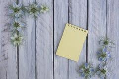 Μια σημείωση για μια ξύλινη επιφάνεια που πλαισιώνεται από τα λουλούδια 5 Στοκ Φωτογραφίες