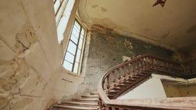 Μια σκάλα με το ξύλινο κιγκλίδωμα σε ένα εγκαταλειμμένο αρχιτεκτονικό κτήριο Η κληρονομιά των αρχιτεκτονικών χρόνων παρελθόντος κ φιλμ μικρού μήκους
