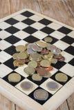 Μια σκακιέρα, αριθμοί και χρήματα Στοκ Εικόνες