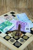 Μια σκακιέρα, αριθμοί και χρήματα Στοκ εικόνες με δικαίωμα ελεύθερης χρήσης