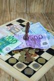 Μια σκακιέρα, αριθμοί και χρήματα Στοκ Εικόνα