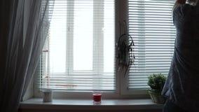 Μια σκιαγραφία γυναικών ανοίγει τη γρίλληα παραθύρου τυφλών το πρωί στο σπίτι απόθεμα βίντεο