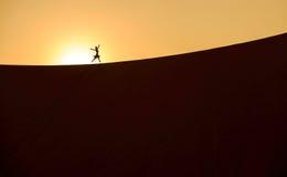 Μια σκιαγραφία ενός κοριτσιού σε μια έρημο sandune στην ανατολή 3 Στοκ Εικόνα