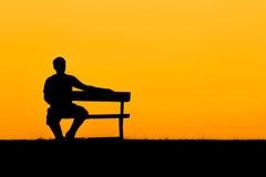 Μια σκιαγραφία της συνεδρίασης ατόμων στον πάγκο στο ηλιοβασίλεμα Στοκ εικόνες με δικαίωμα ελεύθερης χρήσης