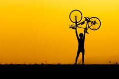 Μια σκιαγραφία του ατόμου που ανυψώνει επάνω το ποδήλατο Στοκ φωτογραφίες με δικαίωμα ελεύθερης χρήσης