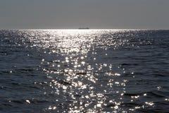Μια σκιαγραφία του φορτηγού πλοίου μακριά στη θάλασσα στην ηλιόλουστη ημέρα στοκ εικόνες