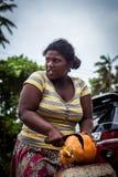 Μια σκοτεινός-ξεφλουδισμένη γυναίκα κόβει μια πορτοκαλιά καρύδα με έν στοκ φωτογραφίες με δικαίωμα ελεύθερης χρήσης
