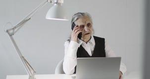Μια σοβαρή ηλικιωμένη γυναίκα με την γκρίζα τρίχα και τις βαθιές ρυτίδες μιλά σε ένα κινητό τηλέφωνο σε ένα γραφείο απόθεμα βίντεο