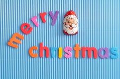 Μια σοκολάτα που καλύπτεται με το περιτύλιγμα προσώπου Santa Clau με τη Χαρούμενα Χριστούγεννα λέξεων Στοκ φωτογραφία με δικαίωμα ελεύθερης χρήσης