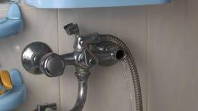 Μια σπασμένη βρύση διαρρέει το νερό, μια διαρροή νερού, μια σπασμένη βρύση, μια κινηματογράφηση σε πρώτο πλάνο φιλμ μικρού μήκους
