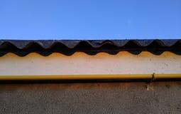 Μια στέγη της κυματιστής πλάκας ενάντια στο μπλε ουρανό και έναν κίτρινο σωλήνα αερίου, που συνδέεται με έναν άσπρο τοίχο σκοτειν στοκ φωτογραφία με δικαίωμα ελεύθερης χρήσης