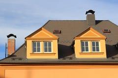 Μια στέγη του μεγάλου σπιτιού πόλεων με δύο καπνοδόχους τούβλων με καλύμματα μετάλλων και δύο πόρτες στεγών και δύο dormers σε έν Στοκ Εικόνες