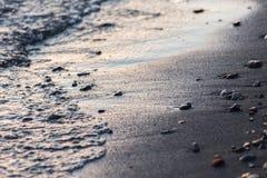 Μια στενή άποψη του νερού σε μια ακτή λιμνών στο ηλιοβασίλεμα, με τις λεπτομέρειες των άμμων και των μικρών στρογγυλών πετρών Στοκ εικόνα με δικαίωμα ελεύθερης χρήσης