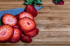 Μια στενή επάνω εικόνα των τεμαχισμένων φραουλών με ολόκληρο ένα μούρο Sli στοκ φωτογραφίες