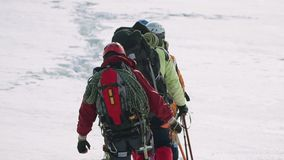 Μια στερεά ομάδα των ορειβατών στο εργαλείο περνά στην απόσταση από το χιόνι αφήνοντας ένα ίχνος φιλμ μικρού μήκους