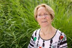 Μια συμπαθητική ηλικιωμένη γυναίκα ονειρεύεται σε έναν όμορφο κήπο Στοκ Εικόνα