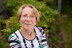 Μια συμπαθητική ηλικιωμένη γυναίκα ονειρεύεται σε έναν όμορφο κήπο Στοκ φωτογραφία με δικαίωμα ελεύθερης χρήσης