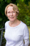 Μια συμπαθητική ηλικιωμένη γυναίκα χαμογελά στη κάμερα σε έναν όμορφο κήπο Στοκ Εικόνα