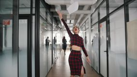 Μια συναισθηματική χαμογελώντας επιχειρησιακή γυναίκα που χορεύει στο διάδρομο γραφείων και που ρίχνει τα έγγραφα στον αέρα απόθεμα βίντεο