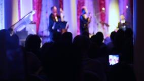 Μια συναυλία τζαζ στη αίθουσα συναυλιών Άνθρωποι που κάθονται στην αίθουσα και που προσέχουν την απόδοση απόθεμα βίντεο