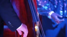 Μια συναυλία τζαζ στη αίθουσα συναυλιών Ένα βιολοντσέλο παιχνιδιού ατόμων Κλείστε επάνω τα χέρια απόθεμα βίντεο