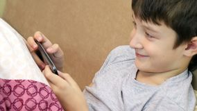 Μια συνεδρίαση αγοριών στον καναπέ και παίζοντας παιχνίδια στο smartphone απόθεμα βίντεο