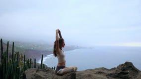 Μια συνεδρίαση γυναικών πάνω από ένα βουνό meditates και κάνει μια χειρονομία με τα χέρια της Maha Sakal Ενάντια στον ωκεανό και φιλμ μικρού μήκους
