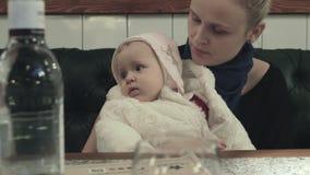 Μια συνεδρίαση γυναικών στον πίνακα με μια κόρη μωρών στην περιτύλιξή της απόθεμα βίντεο