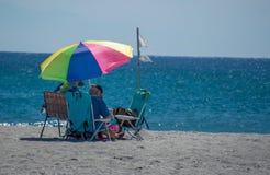 Μια συνεδρίαση ζευγών κάτω από μια ομπρέλα στην άμμο σε μια παραλία στη Φλώριδα Στοκ Εικόνα