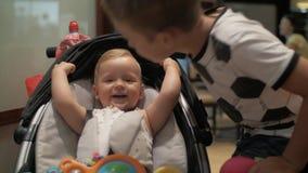 Μια συνεδρίαση κοριτσάκι σε μια μεταφορά μωρών και παιχνίδι με το μεγάλο αδερφό φιλμ μικρού μήκους