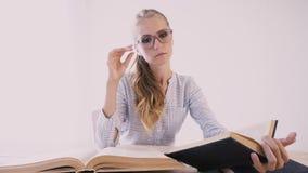 Μια συνεδρίαση κοριτσιών σε έναν πίνακα στο γραφείο διαβάζει πολλά βιβλία απόθεμα βίντεο