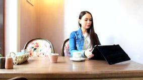 Μια συνεδρίαση κοριτσιών σε ένα café, εργασίες με την ταμπλέτα απόθεμα βίντεο