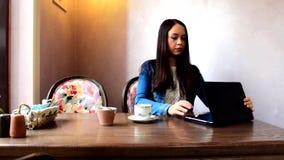 Μια συνεδρίαση κοριτσιών σε ένα café, εργασίες με την ταμπλέτα φιλμ μικρού μήκους