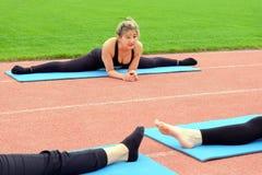 Μια συνεδρίαση νέων κοριτσιών σε έναν διαγώνιο σπάγγο Ασκήσεις ικανότητας με μια ομάδα στο στάδιο τέντωμα Αθλητική άσκηση ομάδας  στοκ εικόνα