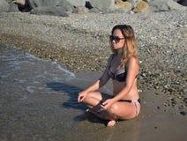 Μια συνεδρίαση νέων κοριτσιών στην παραλία και ηλιοθεραπεία στα γυαλιά στοκ φωτογραφίες