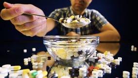 Μια συνεδρίαση προσώπων μπροστά από ένα κύπελλο με τα χάπια πρόκειται να φάει όπως ένα γεύμα απόθεμα βίντεο