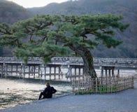 Μια συνεδρίαση ατόμων στην όχθη ποταμού στην περιοχή Arashiyama στο Κιότο, Ιαπωνία Στοκ Φωτογραφίες