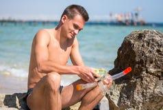 Μια συνεδρίαση νεαρών άνδρων στην παραλία με μια μάσκα για την κατάδυση, κολυμπά με αναπνευτήρα Στοκ Εικόνες