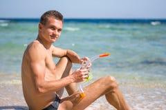 Μια συνεδρίαση νεαρών άνδρων στην παραλία με μια μάσκα για την κατάδυση, κολυμπά με αναπνευτήρα Στοκ Φωτογραφίες