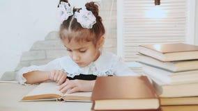 Μια συνεδρίαση παιδιών στον πίνακα οδηγεί το δάχτυλο πέρα από το βιβλίο σελίδων στο σωρό πρώτου πλάνου των βιβλίων φιλμ μικρού μήκους