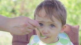 Μια συνεδρίαση παιδιών στον πίνακα των παιδιών Mom που ταΐζει τα δημητριακά μωρών απόθεμα βίντεο