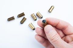 Μια σφαίρα για ένα πυροβόλο όπλο σε ένα ανθρώπινο χέρι σε ένα άσπρο υπόβαθρο Πυρομαχικά στοκ εικόνα