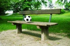 Μια σφαίρα ποδοσφαίρου σε έναν πάγκο πάρκων στοκ εικόνες
